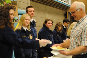 FFA members serve the banquet meal to guests. Dan Cross and Gelene Evans' Foods II class prepared the delicious pork loin and sides.