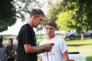 L-S Coach Darin Arkema talks with John Trettin about his sprint time during the Aug. 18 practice.