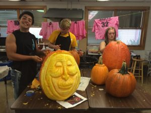 The nearly finished sculpted pumpkin of Mrs. Tara Conover, K-12 art teacher, sits in front of pumpkins being worked on by Nate Stock, Tyson Vander Linden, and Allison Renaud.