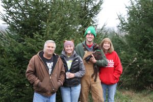 "The Beyer family has been picking the perfect tree from Hackert Tree Farm since it opened. They are pictured with the tree they've tagged this year: From left, Barry, Kelsey, Nick (holding puppy Jaeger), and Linda Beyer. As Linda said, ""It's not Christmas until the Beyer family gets here!"
