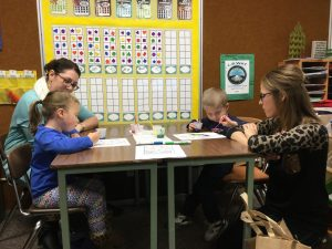 Denise and Katie Staecker, on the left, and Jay and Rebecca Rozendaal participate in a painting activity geared toward helping the children develop control of hand muscles, making writing easier.